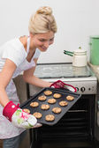 Smiling woman removing a tray of cookies from the oven — Stock Photo