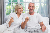 Smiling mature couple with coffee cups sitting on bed — Stockfoto