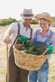 Couple with fresh vegetables in field — Stock Photo