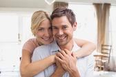 Woman embracing man from behind at home — ストック写真