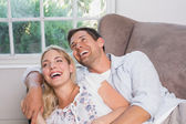 Casual young couple laughing in living room — Stock Photo