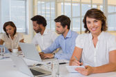 Smiling businesswoman writing notes with colleagues in meeting — Stock Photo