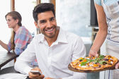 Waitress giving pizza to a smiling man at coffee shop — Stock Photo