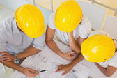 Architects in yellow helmets working on blueprints at office — Stock Photo