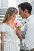 Loving young couple with flowers at home — Stock Photo