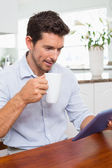 Man using digital tablet while having coffee at home — Stockfoto
