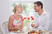 Happy young couple with wine glasses having food — Stock fotografie