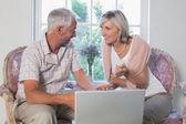Paar bespreken terwijl het gebruiken van laptop thuis — Stockfoto