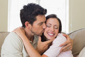 Loving young man kissing woman at home — Stock Photo