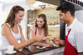 Barista giving pastry to woman at counter in coffee shop — Stock Photo