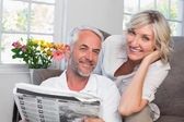 Happy mature couple reading newspaper at home — Stock Photo