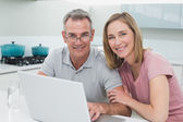 Portrait of a couple using laptop in kitchen — Stock Photo