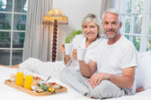 Smiling mature couple with coffee cups sitting on bed — Stok fotoğraf
