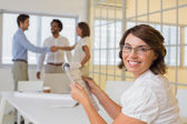 Smiling businesswoman with colleagues shaking hands in background — Stock Photo