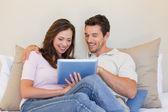 Relaxed couple using digital tablet in living room — ストック写真