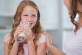 Linda chica bebiendo leche como se ve a su madre — Foto de Stock