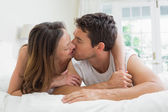 Relaxed couple kissing in bed — Stock Photo