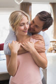 Man embracing woman from behind at home — Stockfoto