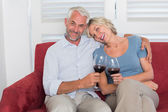 Happy relaxed mature couple with wine glasses in living room — Stock Photo