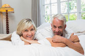 Portrait of a happy mature couple in bed — Stock Photo