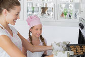 Girl looking at mother remove cookies from oven — Foto Stock