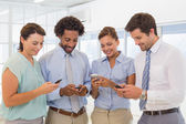 Business colleagues text messaging in office — Stock Photo