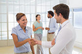 Business people shaking hands with colleagues in office — Stock Photo