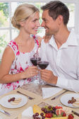 Loving young couple with wine glasses at dining table — Stock Photo