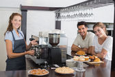 Smiling couple with female cafe owner at coffee shop — Stockfoto