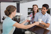 Smiling waitress giving coffee to a couple at coffee shop — Stockfoto