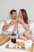 Happy couple having breakfast in bed — Stock Photo