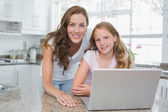 Portrait of a happy mother and daughter using laptop in kitchen — Stock Photo