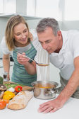 Couple preparing food together in kitchen — Stock Photo