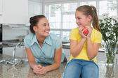 Woman looking at daughter holding apple in kitchen — Stock Photo