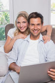 Portrait of casual couple using laptop in living room — Stock Photo