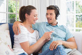Couple listening music with mobile phone on couch — Stock Photo