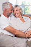 Mature couple looking at each other in living room — Stock Photo