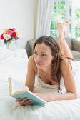 Fulla längd av avslappnad kvinna läser en bok i sängen — Stockfoto