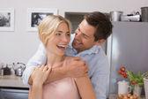 Hombre alegre abrazando desde atrás mujer en cocina — Foto de Stock