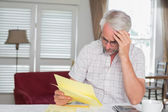 Serious mature man sitting with home bills — Stock Photo