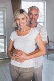 Mature man embracing woman at home — Stock Photo