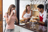 Woman drinking coffee with friend and male barista in coffee shop — Stock Photo