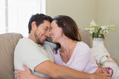 Cheerful loving couple on couch at home — Stock Photo