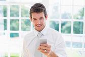 Businessman text messaging at home — ストック写真