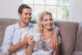 Relaxed loving couple with coffee cups in living room — Stock Photo