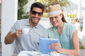 Smiling couple with coffee cup using digital tablet at cafe — Stock Photo