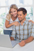 Happy couple doing online shopping at home — Stock Photo