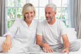 Smiling mature couple sitting on bed at home — Stockfoto