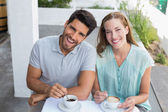 Happy young couple with coffee cups at cafe — Stock Photo