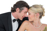Bride and groom with head to head over white background — Stock Photo